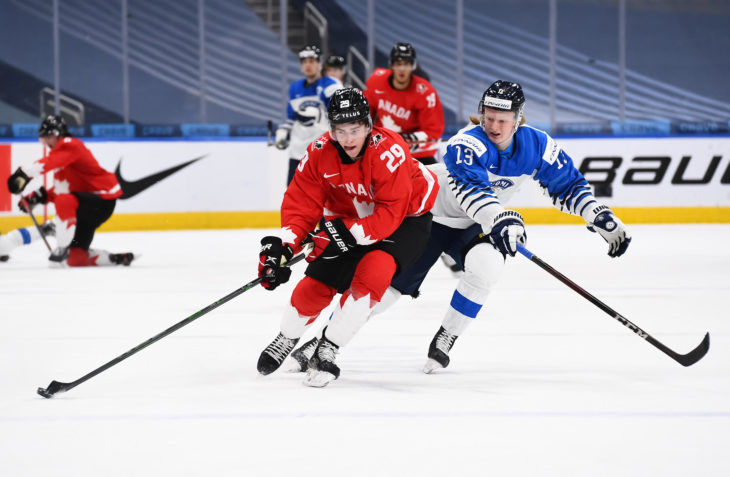 EDMONTON, AB CANADA - DECEMBER 31: Canada's Jack Quinn #29 skates with the puck while Finland's Roby Jarventie #13 chases him down during preliminary round action at the 2021 IIHF World Junior Championship at Rogers Place on December 31, 2020 in Edmonton, AB Canada. (Photo by Andrea Cardin/HHOF-IIHF Images)