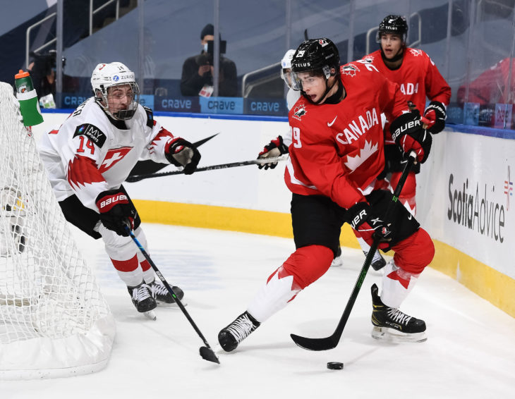 EDMONTON, AB CANADA - DECEMBER 29: Canada's Jack Quinn #29 plays the puck while Switzerland's Lorenzo Canonica #14 defends during preliminary round action at the 2021 IIHF World Junior Championship at Rogers Place on December 29, 2020 in Edmonton, AB Canada. (Photo by Andrea Cardin/HHOF-IIHF Images)