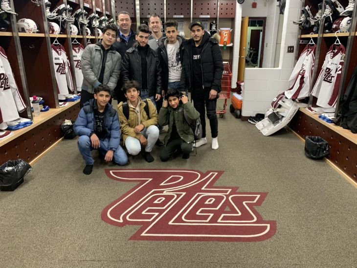 Petes GM Mike Oke (back left) and Head Trainer/Equipment Manager Brian Miller (back right) give a dressing room tour to a group of new Canadians.