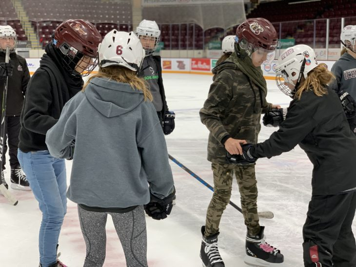 Members of the PGHA Peewee AA Ice Kats lend helping hands to new Canadians as they skate for the first time.